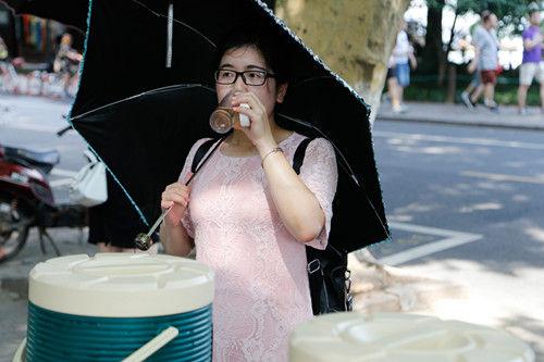 图为:一位游客正在饮用刚刚接的茶水。王远