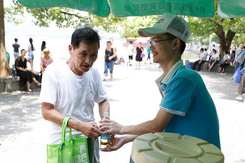 图为:志愿者正把接好的茶水递给一位老年游客。王远