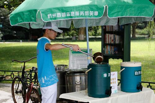图为:一位志愿者正在往茶桶里加茶水。王远