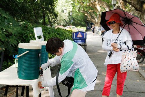 图为:游客正在用瓶子接茶水。王远