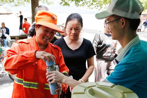图为:志愿者正把刚接好的茶水递给环卫工人。王远