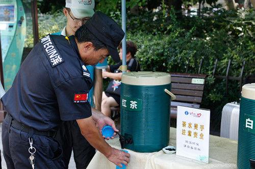 图为:一位安保工作者正在接茶水。王远