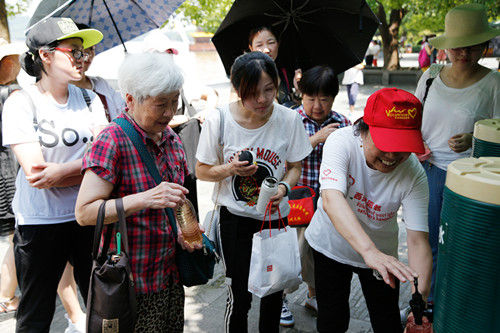 图为:游客正站在凉茶摊前按序接茶水。王远