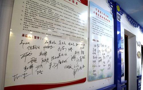 """图为:44名法官及其家属在""""公正廉洁司法承诺墙""""上郑重的签下自己的名字。李江林"""