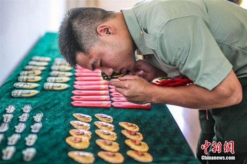 """9月5日,宁波武警一名退伍老兵吻别领花和服装标识。当日,浙江武警迎来一年一度的""""退伍季"""",退出现役的老兵纷纷卸下警衔,踏上返乡之路。中新社发 殷福军 摄"""