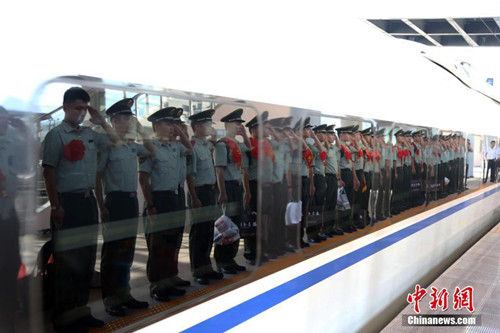 """9月5日,丽水武警官兵在火车站送别战友。当日,浙江武警迎来一年一度的""""退伍季"""",退出现役的老兵纷纷卸下警衔,踏上返乡之路。中新社发 罗圣雄 摄"""
