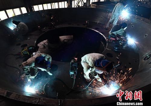 2017年7月份中国制造业采购经理指数(PMI)为51.4%。图为厦工(三明)重型机器有限公司电焊工人正在焊接盾构机盾体。中新社记者 张斌 摄