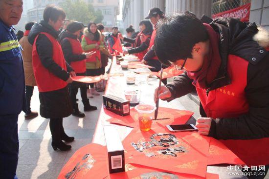 在青田火车站,志愿者为旅客们写春联。