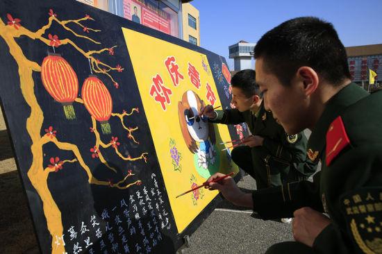 """图为官兵们手绘""""欢庆春节""""板报。 颜石斌 摄"""