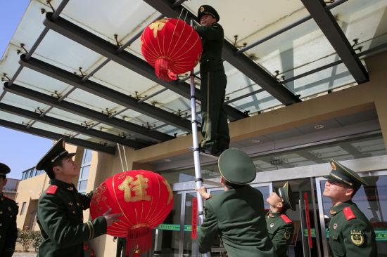 图为官兵们挂起红灯笼。 颜石斌 摄
