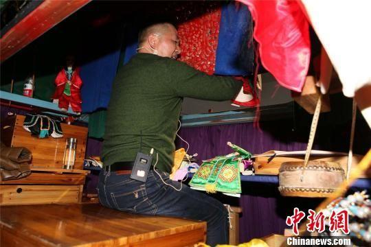 艺人藏在屏后,手执布袋木偶,双脚踏锣 叶其念 摄