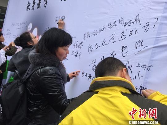 捐赠者家属在签名墙上写下哀思。 童笑雨 摄