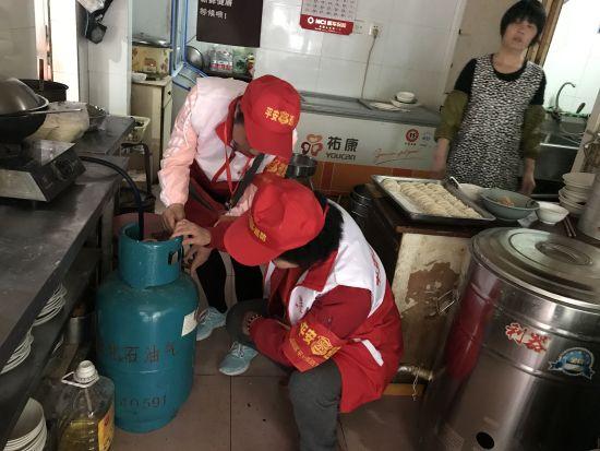 西湖区巡逻志愿者正在对一家饭店的煤气罐进行安全排查。 西湖区政法委综治办 供图