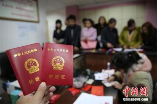 资料图:在四川省内江市东兴区婚姻登记处,新人在展示刚领取的结婚证书。 兰自涛 摄