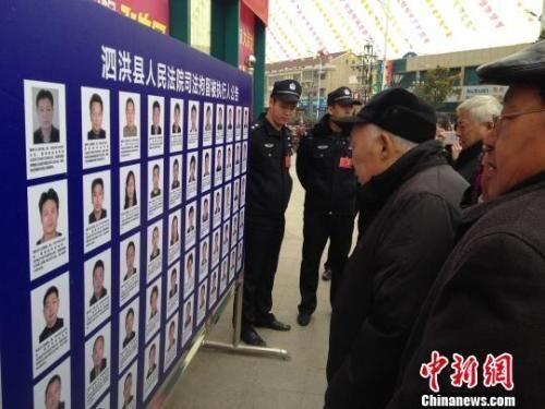 """资料图:民众围观被曝光的""""老赖"""" 刘林 摄"""