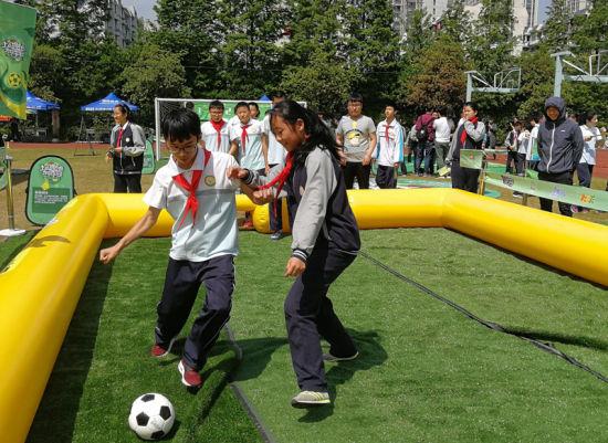 学生体验全国中学生阳光体育足球训练成果交流展示活动中的踢足球项目。 马悦宁 摄