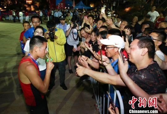 图为市民群众纷纷为100公里组冠军梁军点赞 官射群 摄