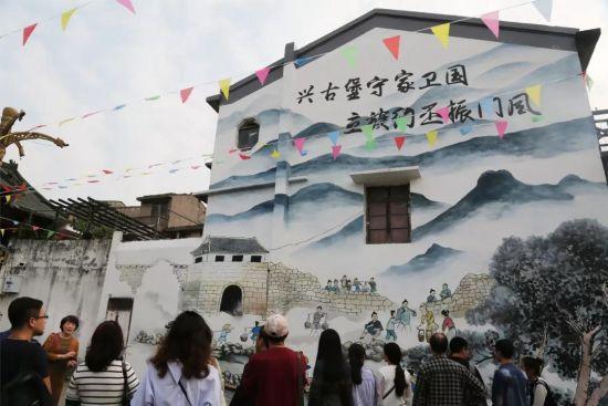 """市民在永昌堡""""筑堡图""""大型墙绘前驻足参观。龙湾宣传部提供"""