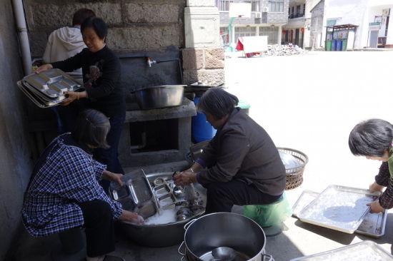 吃完午饭,不少老人主动帮忙洗餐盘。陈诺 摄