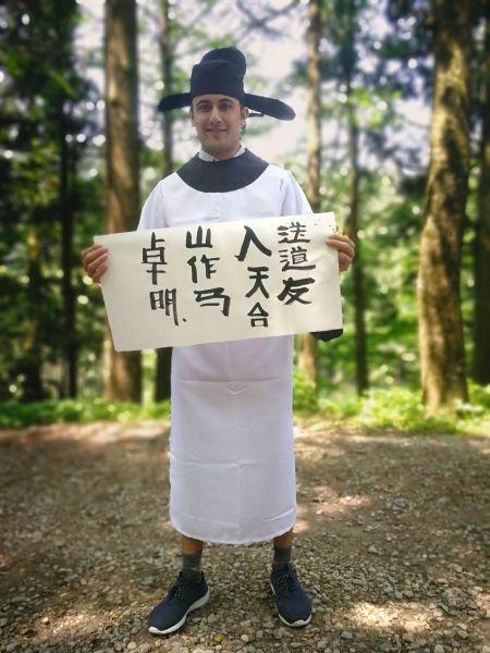 图为外国游客身穿中式服装写下的毛笔字 主办方供