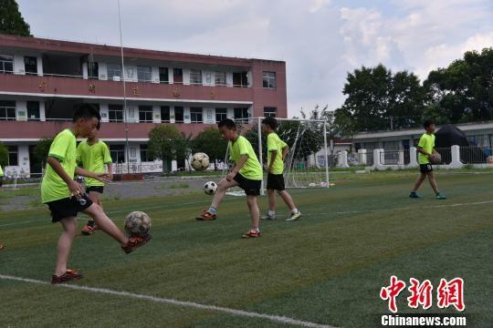 图为:红旗完全小学足球队球员在操场上训练 范宇斌 摄