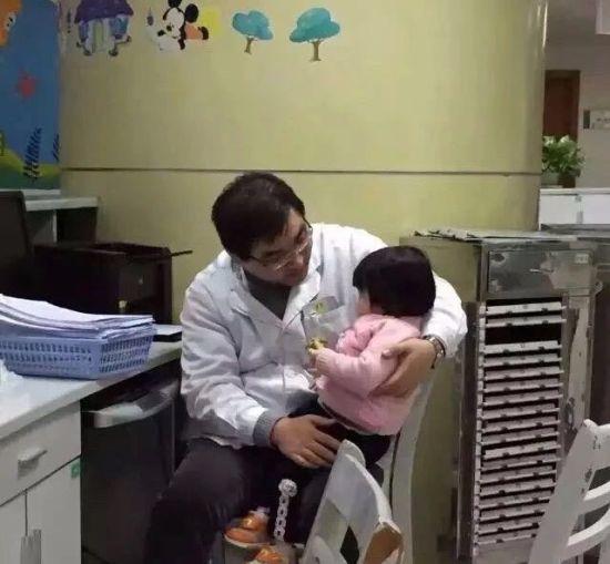 图为男孩父亲抱着儿童患者为其讲故事。 绍兴市人民医院供图
